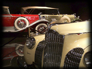 1939 Packard One-Twenty Victoria Convertible with Darrin coachwork and Packard and Lincoln in the background